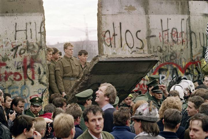 (FILES) - Picture taken on November 11, 1989 shows West Berliners crowd in front of the Berlin Wall as they watch East German border guards demolishing a section of the wall in order to open a new crossing point between East and West Berlin, near the Potsdamer Platz. Germany on November 7, 2014 kicks off a weekend of celebrations marking the 25th anniversary of the epochal fall of the Berlin Wall with millions expected to descend on the reunited capital. AFP PHOTO / GERARD MALIE